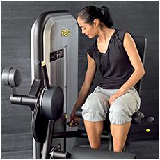 Eine sportliche Frau, welche an der Beinpresse Ihre Beine trainiert und gerade Ihr optimales Trainingsgewicht wählt