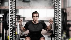 Athlet macht in einem Trainingsgerüst Kniebeugen