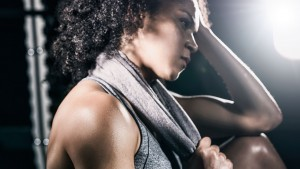 Erschöpfte Frau vom Training, welche Ihren Kopf hält